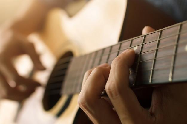 La mano del hombre tocando la guitarra acústica, concepto musical