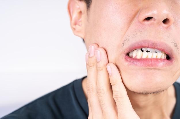 Mano de hombre tocando su mejilla que sufre de dolor de muelas.