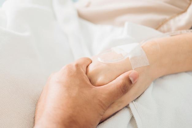 La mano del hombre toma las manos de la mujer para alentar a la solución salina del paciente acostado en la cama del hospital proporcionar nutrientes vasculares.