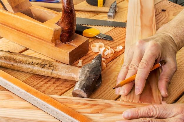 La mano del hombre trabajando en el escritorio de carpintero y herramientas de trabajo
