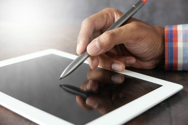 La mano del hombre trabajando en tableta digital con lápiz gráfico