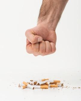 La mano del hombre tratando de aplastar los cigarrillos sobre fondo blanco