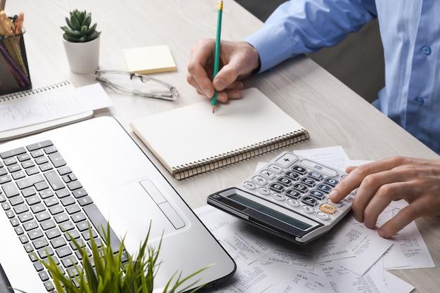 La mano del hombre usando la calculadora y la escritura tomar nota con calcular el costo y los impuestos en la oficina en casa.