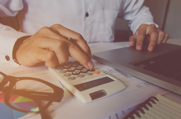 Mano del hombre usando una calculadora financiera