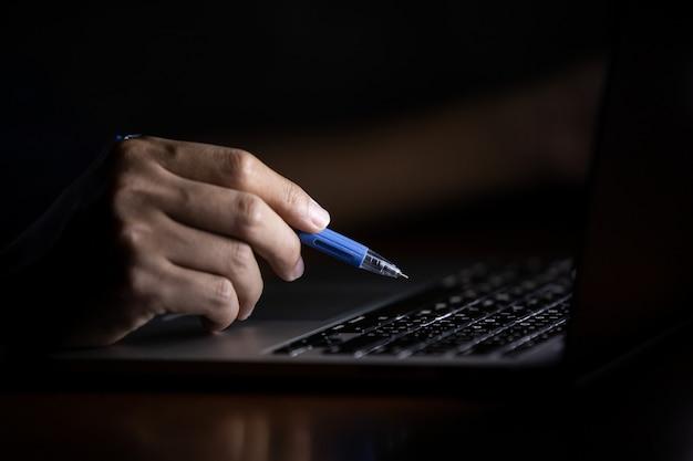 Mano de un hombre usando una computadora portátil trabajando en la noche