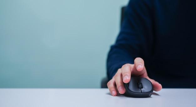 Mano del hombre usando el cursor del mouse para desplazarse por la página web o trabajar en la computadora
