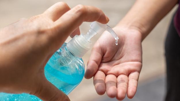 Mano de hombre usando dispensador de gel desinfectante para lavado de manos, contra coronavirus novedoso o enfermedad de virus corona (covid-19) en público interior