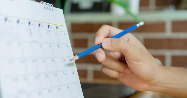Mano del hombre usando la pluma para escribir el calendario en el calendario para hacer una cita en casa para trabajar desde casa