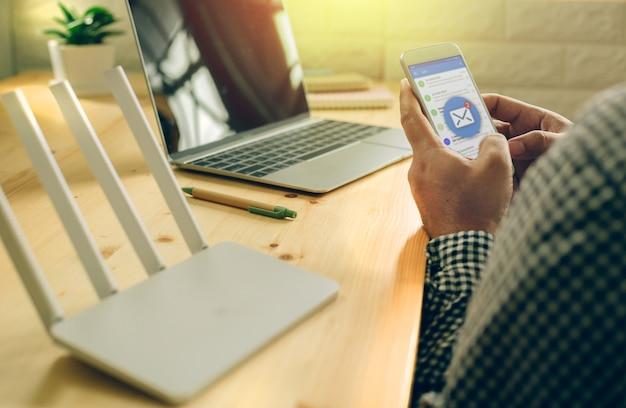 Mano de hombre usando teléfono móvil con aplicación de correo electrónico