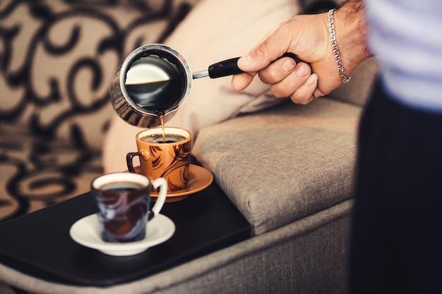 La mano de un hombre vierte café en una taza junto a la cama