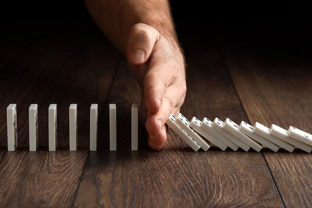 La mano de los hombres detuvo el efecto dominó, sobre una madera marrón.