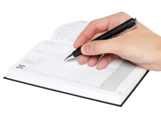 La mano de los hombres escribe algunos en organizador. aislado sobre blanco.