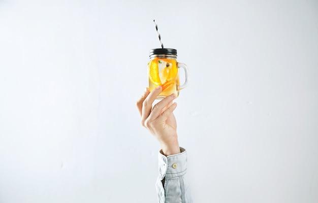 La mano de los hombres presenta limonada fría casera de naranjas, agua con gas y cubitos de hielo aislados en blanco.
