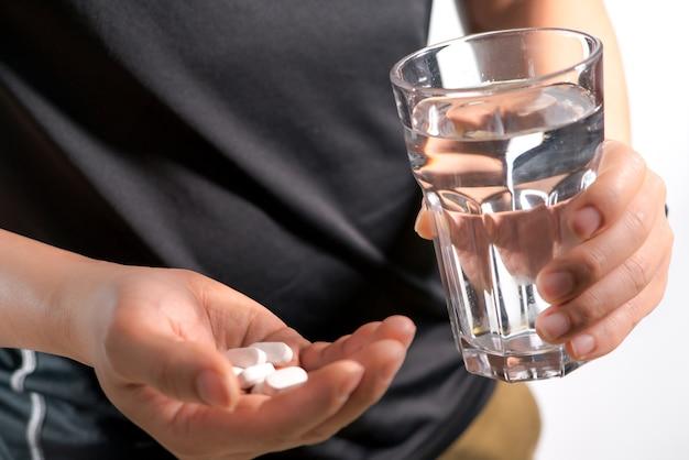 Mano de hombres sosteniendo la medicina con vidrio de concepto de recuperación de medicina de agua