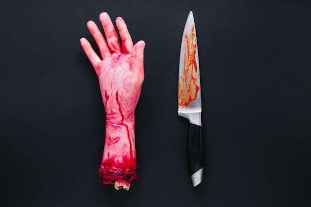Mano humana artificial en sangre y cuchillo