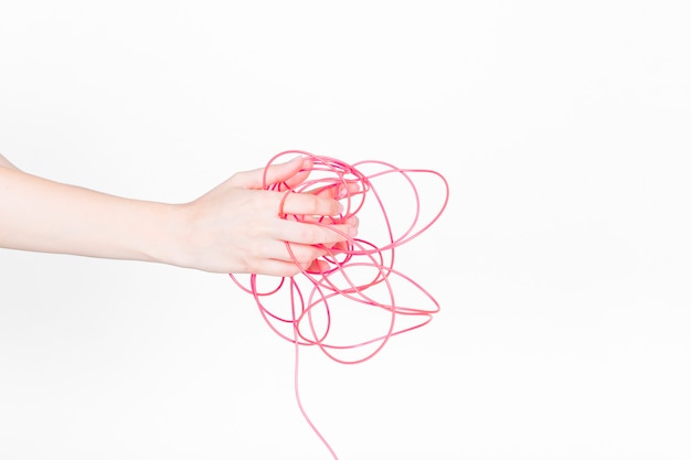 Mano humana con cable rojo enredado