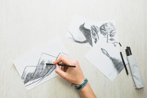 Mano humana dibujando en papel con palillo de carbón cerca de dibujo dibujado a mano hermosa