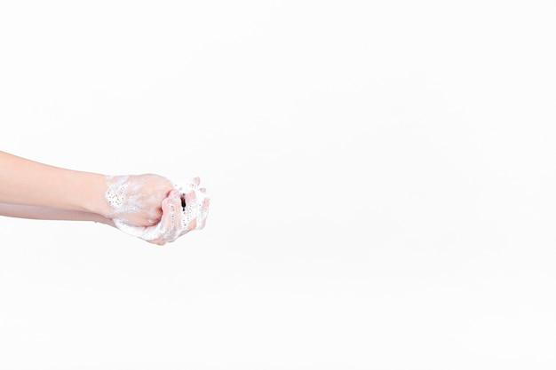 Mano humana en espuma de jabón sobre fondo blanco