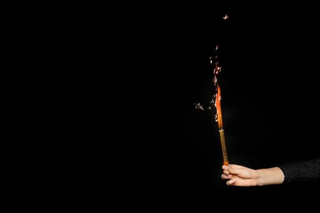 Mano humana con fuegos artificiales en llamas