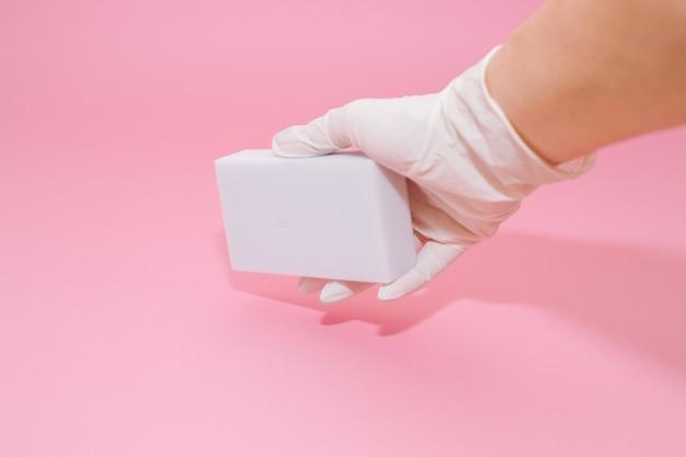 La mano humana en el guante blanco sostiene una esponja doméstica de melamina blanca para limpiar sobre fondo rosa.