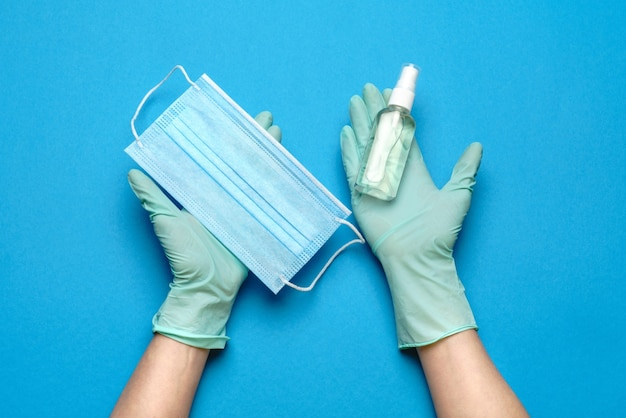 Mano humana en guante protector con máscara protectora facial y spray desinfectante de manos con alcohol en azul