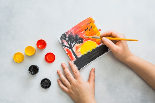 Mano humana pintando hermosos paisajes vistos en papel