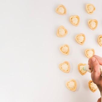 Mano humana poniendo crema fresca en delicioso corazón forma tartaleta