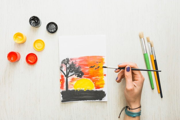 Mano humana que pinta una puesta del sol hermosa de la naturaleza vista en el papel con colores de agua