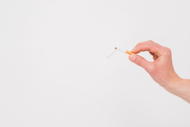 Mano humana que sostiene el cigarrillo roto en el contexto blanco