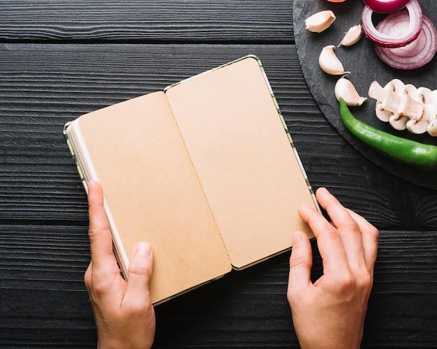 Mano humana que sostiene el diario cerca de chile; dientes de ajo; cebollas y champiñones sobre superficie de madera negra.