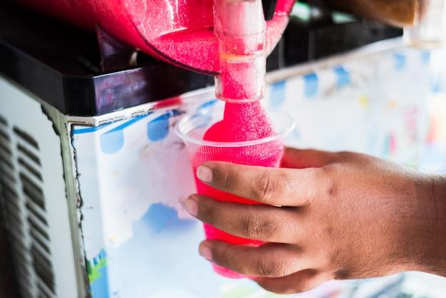 Mano humana sirviendo una bebida fangosa de una máquina fangosa.