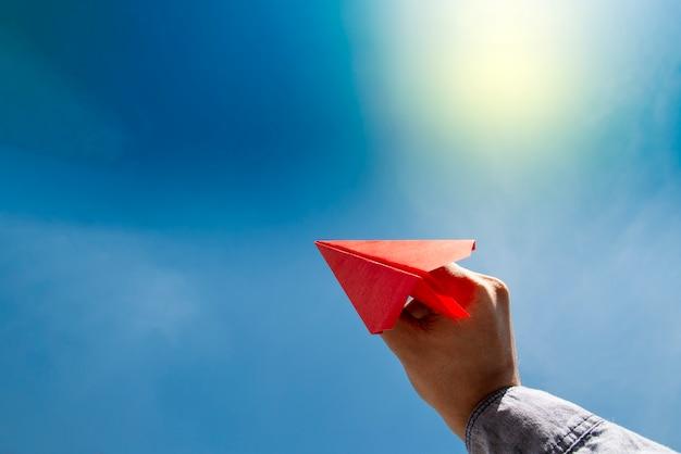 Mano humana sosteniendo avión de papel rojo