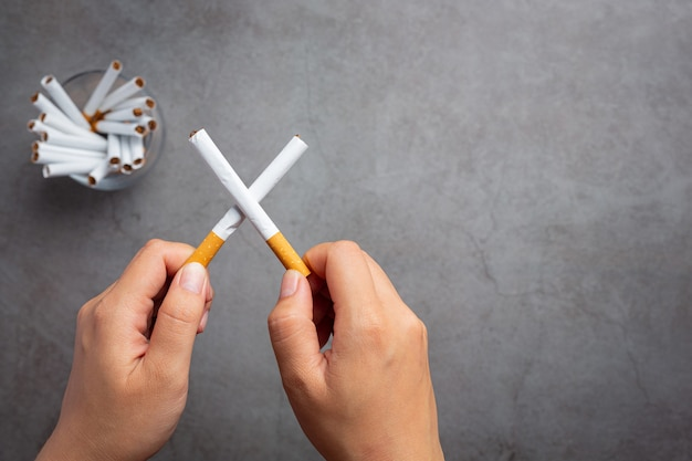 Mano humana sosteniendo el cigarrillo concepto del día mundial sin tabaco.