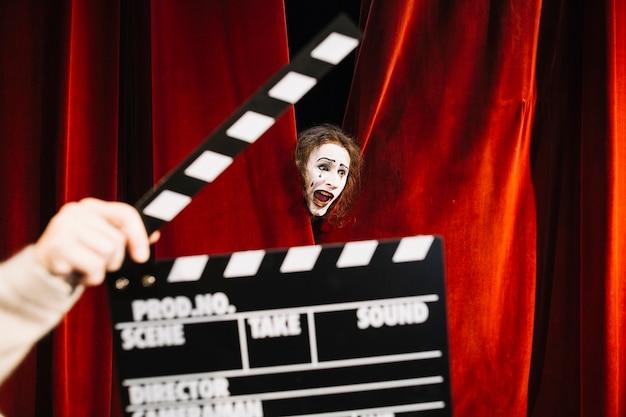 Mano humana sosteniendo claqueta frente a artista mimo macho actuando detrás de la cortina roja