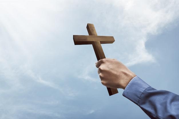 Mano humana sosteniendo la cruz cristiana