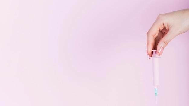 Mano humana sosteniendo la jeringa de plástico sobre fondo rosa