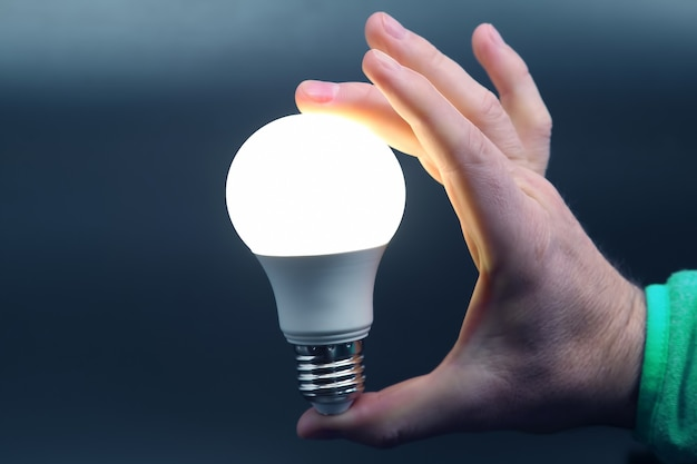 Mano humana sosteniendo la lámpara led incluida en negro. industria de la electricidad y el led
