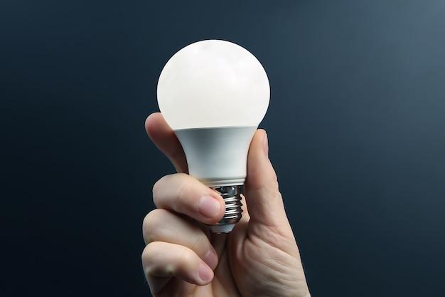 Mano humana sosteniendo la lámpara led incluida en una oscuridad. industria eléctrica y led