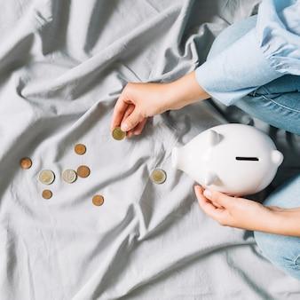 Mano humana sosteniendo monedas y piggybank