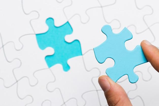 Mano humana sosteniendo piezas de puzzle azul sobre fondo de cuadrícula puzzle blanco
