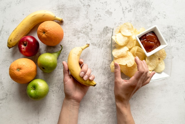 Mano humana sosteniendo plátano y papas fritas en superficie de cemento