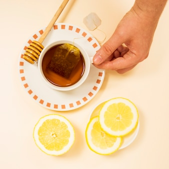 Mano humana sosteniendo una taza de té saludable
