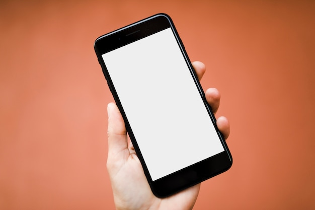 Mano humana sosteniendo teléfono inteligente con pantalla en blanco