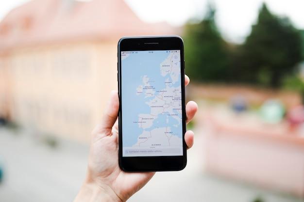 Mano humana sosteniendo el teléfono móvil con la navegación del mapa gps en la pantalla