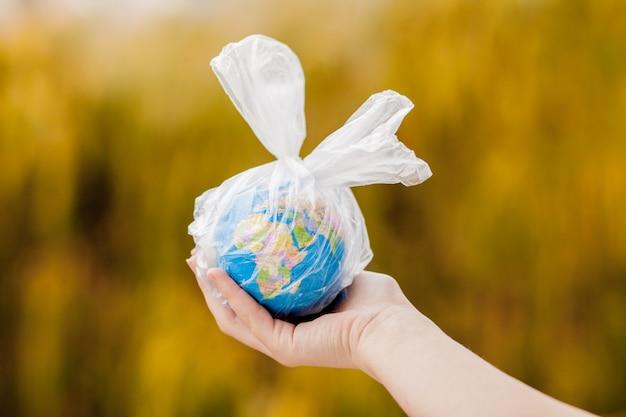 Mano humana sostiene el planeta tierra en una bolsa de plástico