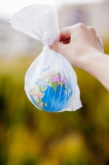 La mano humana sostiene el planeta tierra en una bolsa de plástico.