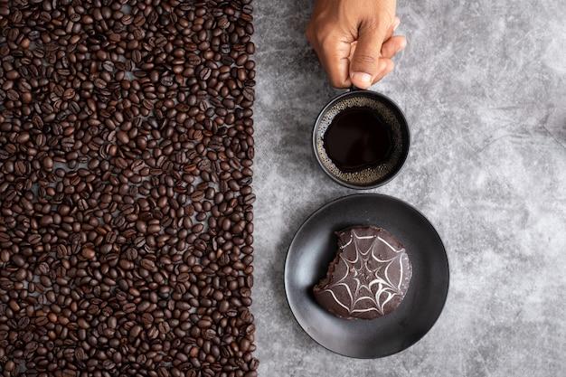 La mano humana sostiene la taza de café y la torta de chocolate con los granos de café en el fondo de la textura del cemento.