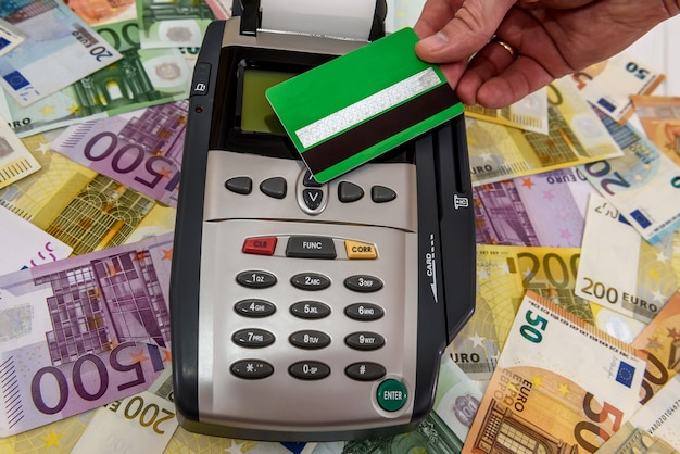 Mano humana con tarjeta de crédito y terminal con billetes en euros
