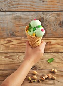 Mano infantil sosteniendo un cono de helado de pistacho