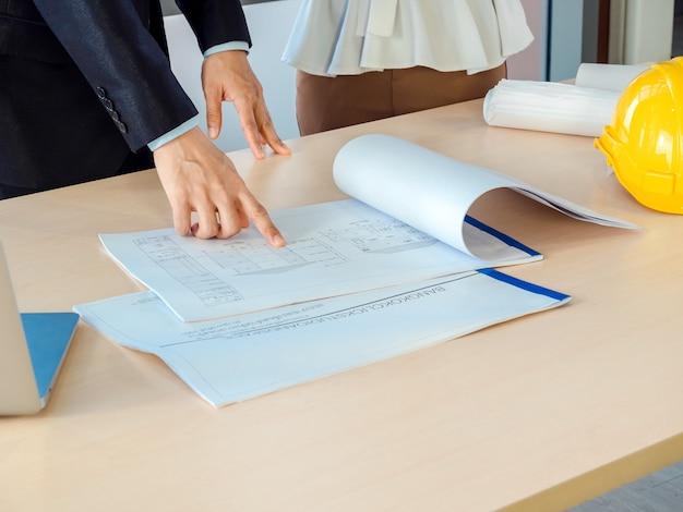Mano del ingeniero señalando el plano en el escritorio de madera con casco de seguridad y computadora portátil en el lugar de trabajo